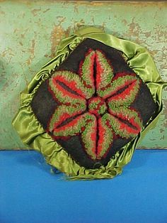 This is a pincushion pillow, an example of Amish plush work. This has a black wool crepe base with red, green, and brown wool yarns and a satin
