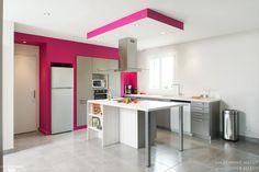 Une cuisine ouverte avec îlot central et touche de couleur rose fushia.