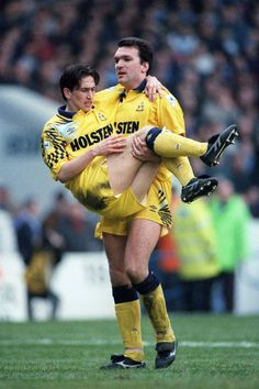 Gillingham manager Justin Edinburgh is carried off the pitch by team-mate Neil Ruddock after the Tottenham defender was injured during their 4-2 win over Manchester City in the FA Cup match in March 1993