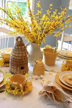 WHITE DISHES: with yellow accents (bee patterned), and accents of bee skeps, and little bees.  white pitcher with yellow flowers ( could be tulips, daylilies, daisies, black-eyed susans, sunflowers.)