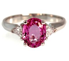 This lovely pink Sapphire is set in 14k white gold and flanked by two trillion cut diamonds averaging VS2 clarity and G color. The diamonds weigh 0.30 carat total weight.