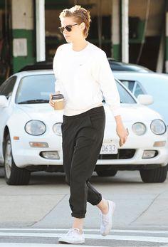 Kristen Stewart wearing a white long-sleeve sweatshirt, black trousers, and white sneakers