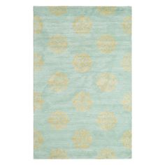 Add a lovely touch to your living room or den with this hand-tufted New Zealand wool rug, showcasing a scrolling medallion motif against a turquoise backgrou...