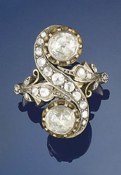 A diamond ring   The two rose-cut diamond collets to a rose-cut diamond crossover design mount and floral shoulders  [Personally, I think this looks Edwardian or possibly Victorian, but what do I know?]