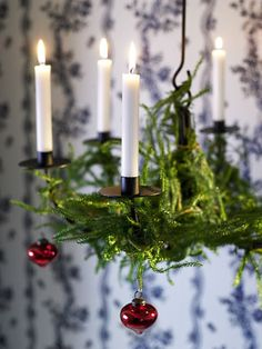 Fresh evergreenery and red ornaments decorating a hanging candelabra.