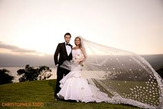 bride and groom sunset photo with cathedral veil at trump national golf club…