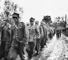 Polish prisoners of war march down a muddy dirt road in Poland. Two German soldiers walk alongside them.