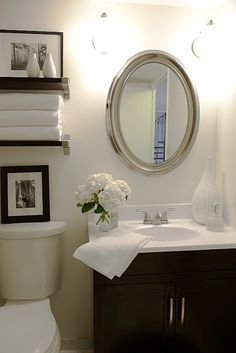 INSPIRATION; Half Bath Design. Gray walls.  Brushed and satin nickel fixtures. Thrift store mirror and silver spray paint. Espresso vanity with white ceramic counter top. Colorful rug. About $950.