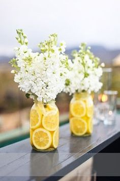 lemon centerpiece and white flowers. Add a blue ribbon or blue table liner, so sweet. This would look great at a bar, breakfast table with oranges.