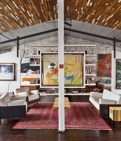 Beneath a recycled-wood ceiling and centered by a Bokhara rug, the living area contains furniture of their own design.   Photo by Ball &a...