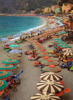 Umbrellas form a curved line on the beach in Monterosso, one of the five towns in Italy's Cinque Terre La Spezia Liguria