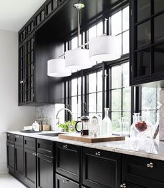 Black kitchen - Lonny mag....Love the black cabinets with all white walls, light fixtures etc..
