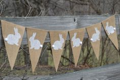 Bandera de conejo ♥ ♥ Una dulce adición a tus decoraciones de primavera o en cualquier momento! Se hace en arpillera natural tamaño 6 x 9. Los conejos han sido pintados de blancos con la cola de algodón. El banner es 3 pies de largo. Cosido en una hebra de hilo de yute.
