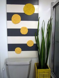 striped plywood art with huge fabric rosettes. this makes me droll over the pop of color. Maybe in my bathroom?