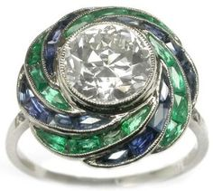 This is a magnificent example of an Art Deco period ring. The ring is set with an old mine cut diamond in the center accentuated by approximately 0.70ct of sapphires and approximately 0.70ct of emeralds. The approximate weight of the center diamond is 1.75ct. The color of the diamond is J and the clarity is VS1. The ring features a beautiful open work gallery