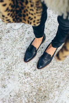 Zwarte loafers met donkere jeans gecombineerd met een luipaardjas voor een stoerder contrast. #trend #loafers