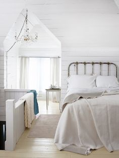 This homeowner whitewashed the walls in her attic to heighten the drama of its pointed arch. #decoratingideas #bedroomdecor