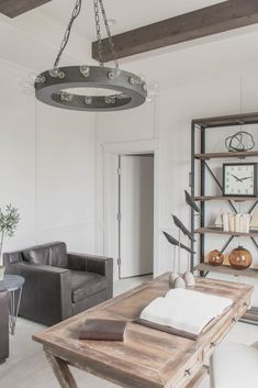 Neutral office with wood beams, white walls and wood and leather accents via…
