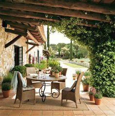 00276916. Comedor bajo el porche con sillas de fibras y rodeado de plantas_00276916