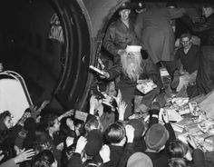 Young Berliners get a treat at the U.S. Army's Tempelhof Airport in Berlin, Dec. 15, 1948. Christmas gifts from a flying Santa, Lt. John Konop of Astoria, NY. This is the first planeload of gifts to be distributed to Berlin children under the Air Forces Christmas program, Operation Santa Claus. The gifts were donated by people in the United States and flown to Berlin via the air lift.