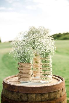 I love this idea simple but gorgeous bunches of gypsophila displayed in glass DIY jars/vases with hesian and twine Perfect on a beer barrel for your country /rustic wedding