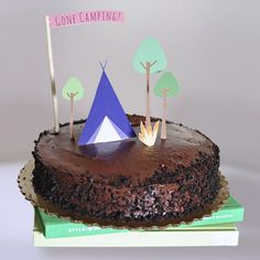 See how easy it is to turn a store bought cake into a fun DIY Camping theme by simply cutting out paper!