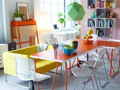 Ruokailutila, jossa kaksi oranssia pöytää ja valkoiset tuolit ja niiden yllä vihreä kattovalaisin.
