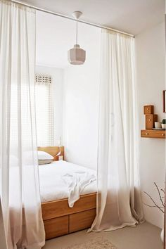 Small bedroom with white curtains and wooden accents.