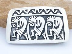 Belt buckle that features 3 Kokopellis that are playing their flutes to chase away the harsh winter weather.