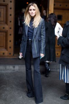Olivia Palermo wears a tailored blazer, skinny flared denim, and a mock neck top.