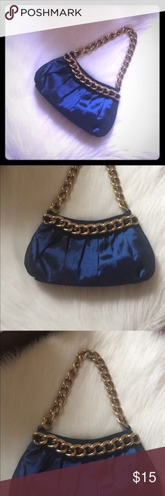 Midnight Blue/Gold Chain Purse Pintucked blue satiny clutch with gold chain piping and handle; zip top with small interior pocket. Measurements are approximately 10 inches width at the widest spot of the clutch and 13/14 inches in length from the top of the chain handle. The perfect purse for a night out-small and compact but roomy enough for the essentials. Fits perfectly under the shoulder. 100% polyester body. Purchased at a boutique and is unbranded. Perfect condition. Feminine and fun…