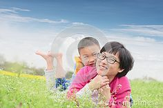 Chinese happy family lying on lawn in spring with blue sky background