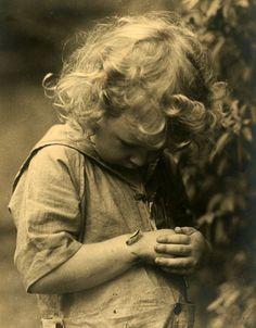 Young child admiring a caterpillar.