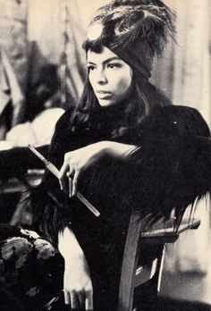 Bianca with head wrap, feather and cigarette holder.