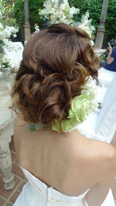 柔らかな編み込みアップスタイル+前髪は斜めに流しながらツイストして後ろ側へ合流させます。反対側にも編み込みアレンジを。 葉生花を飾ります。 ヘアセットはあくまでも髪の毛は柔らかく、ウエービーな印象で作り上げます。 後ろ部分のカールの凹凸感が出る様にエアリー感を含ませてセット。