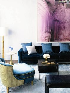 Klassiek interieur waarin de lichte, gladde achterwand en het grote, moderne kunstwerk (met toch een typisch klassieke pruimtenpaars) zorgen voor een eigentijdse look.