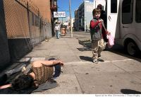 Daragh Hughes (7), passes a homeless woman passed out on Turk St. Photo by Theo Rigby/Special to The Chronicle -ONE TIME USE ONLY- Photo