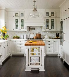 realistic sized kitchen. Bright and Cheerful. Marble subway, dark floors, butcher block counter.