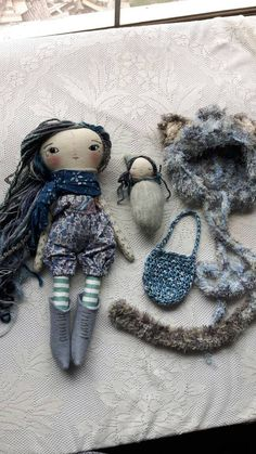 Joy doll - 17ish handmade cloth doll. This sweet joy girl has long grey, blue and purple hair that can be gently styled as you like. Her face and details are stitched by hand with love. She has a sweet baby in a bag. Her cat hat and tail are crocheted with love by hand and she has awesome poof shorts and boots. She is super darling. this line of dolls is my new favorite. They are substantial enough to hug, but darling enough for play. Their ears are stitched in to the body and are not…