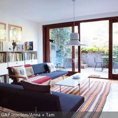 Vom Wohnzimmer führt eine große gläserne Schiebetür zum Innenhof, dadurch fällt viel natürliches Licht in den Raum. Das USM-Sideboard und die Sitzmöbel  …