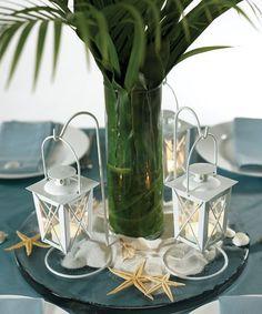 Summer table, tall cylinder vase, shells, sea stars, sand on platter