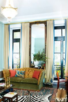 """""""If there is any theme or idea to this apartment, it was simply a return to the building's original style. I am so tired of contemporary,"""" says Merck. """"I believe the folding sofa by the French doors is early 1800s and it's still the original tapestry. The mirrors and the chandelier are thought to be original to the building, while the rug is something that was passed down to me from my grandmother."""""""