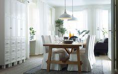Zona pranzo con tavolo per 8 persone in rovere e sedie con fodere lunghe bianche.