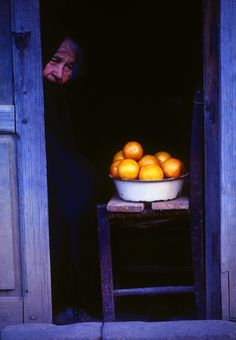 Bruce Muirhead:  Old Woman in doorway, Patzcuaro, Mexico.  While walking the narrow streets of Patzcuaro, next to the scenic lake of the same name, I passed this doorway with an elderly woman selling some large oranges. Her black shawl identified her as a widow. The lack of social security services in Mexico has probably necessitated her attempt to supplement her meager income. Yes, I did buy a couple of them – delicious!