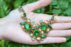 Vintage faux pearl and rhinestone necklace by Hobe, circa 1960. This necklace has green and smoky rhinestones and faux golden pearls set in gold tone metal.