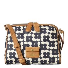 Orla Kiely's Textured Vinyl Flower Shadow Dot Print Iris Bag in Navy. Flower Shadow Dot' print textured vinyl bag with leather trims and small leather pocket detail to front. Leather strap is adjustable in length. Zip pocket on back. Two way zip to close. Inside details include sand colored linear stem cotton jacquard lining, small zip pocket, key chain and mobile pockets.