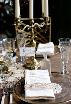 Vintage-looking dishware and antique doilies from a local thrift store add charm to each place setting. Place cards are secured onto pieces of twisted wire and displayed in vintage bottles.