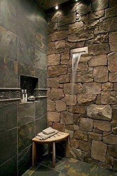 Dashing Shower With Stone Wall And Wooden Stool