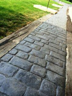 Pavimento de hormigón estampado con ankare zaline gris pizarra en textura adoquín london con maestras de traviesas de madera
