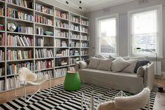 salon scandinave avec tapis rayé et grande bibliothèque